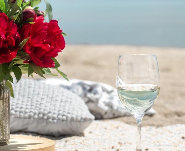 Romantyczny piknik nad morzem z kwiatami i kieliszkami szampana. pojęcie wakacji.