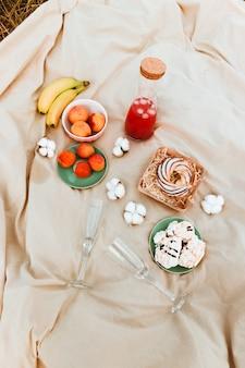 Romantyczny piknik z ciastem deserowym, bezą, bananem, owocami, lampką szampana i butelką czerwonego napoju na świeżym powietrzu w polu w słoneczny dzień