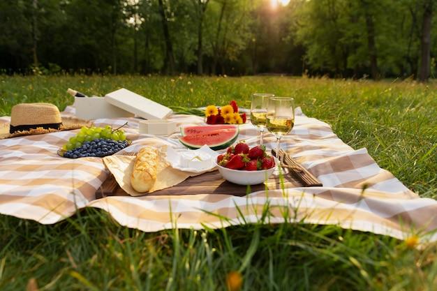 Romantyczny piknik z natury. piękno zachodzącego słońca, świeżych owoców i wina.
