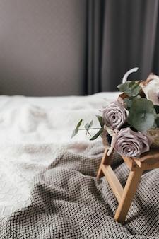 Romantyczny poranek. stolik kawowy drewniany z kwiatami na łóżku z kocem. róże bzu z eukaliptusem i ukwiałami. odcienie szarości wnętrza.