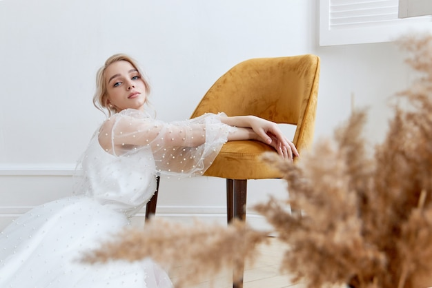 Romantyczny portret kobiety na podłodze w pięknej długiej białej sukni