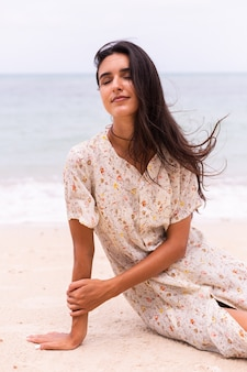 Romantyczny portret kobiety w długiej sukni na plaży w wietrzny dzień pochmurny.