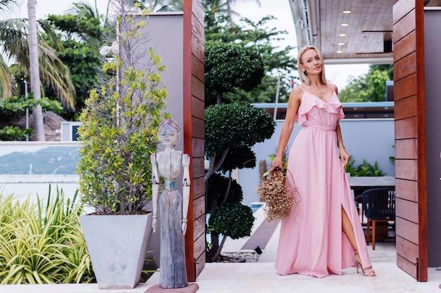 Romantyczny portret kobiety w różowej wieczorowej ślicznej sukience trzymaj dzikie kwiaty poza luksusową tropikalną willą piękna kobieta z bukietem