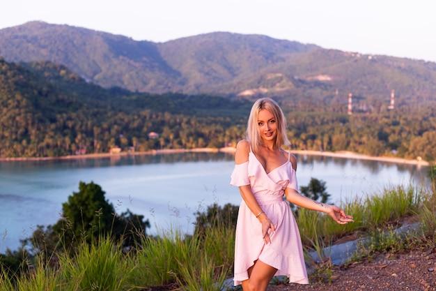 Romantyczny portret młodej kobiety rasy kaukaskiej w letniej sukience relaksującej się w parku na górze z niesamowitym tropikalnym widokiem na morze kobieta na wakacyjnej podróży po tajlandii szczęśliwa kobieta o zachodzie słońca