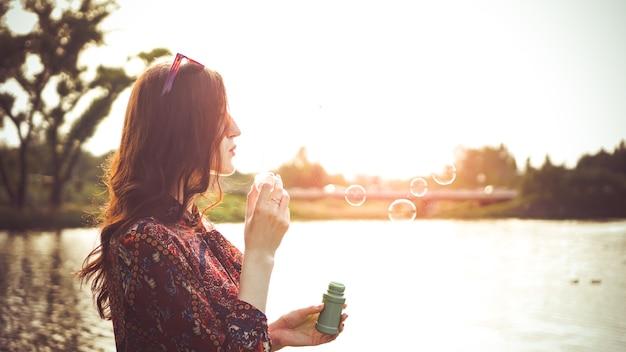 Romantyczny portret młodej kobiety z balonów mydlanych. słoneczna dolina i rzeka w letni dzień