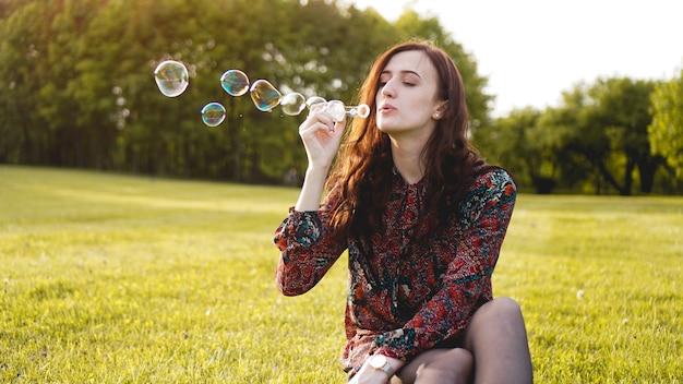Romantyczny portret młodej kobiety z balonów mydlanych. słoneczna dolina w letni dzień