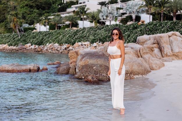 Romantyczny portret młodej spokojnej szczęśliwej szczupłej kobiety rasy kaukaskiej w krótkiej bluzce i spodniach ustawionych samotnie na skalistej tropikalnej plaży o zachodzie słońca