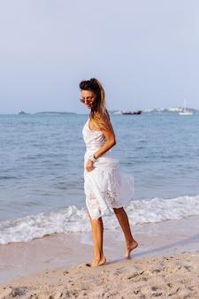 Romantyczny portret opalonej kobiety w białej letniej sukience na tropikalnej plaży o zachodzie słońca