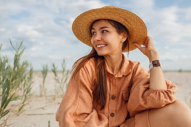 Romantyczny portret uśmiechnięta kobieta w słomkowym kapeluszu i stylowej lnianej sukience. marzycielska dziewczyna chłodzi w pobliżu oceanu. letni trend w modzie.