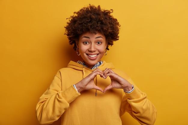 Romantyczny portret zadowolony ładna kobieta pokazuje symbol miłości