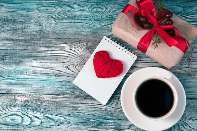 Romantyczny przytulne tło z czerwonym sercem, pudełkiem i filiżanką kawy.