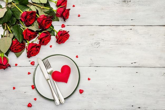 Romantyczny stół obiadowy. koncepcja miłości na walentynki lub dzień matki, sztućce ślubne. bukiet świeżych róż burgundowych, tło białe deski drewniane