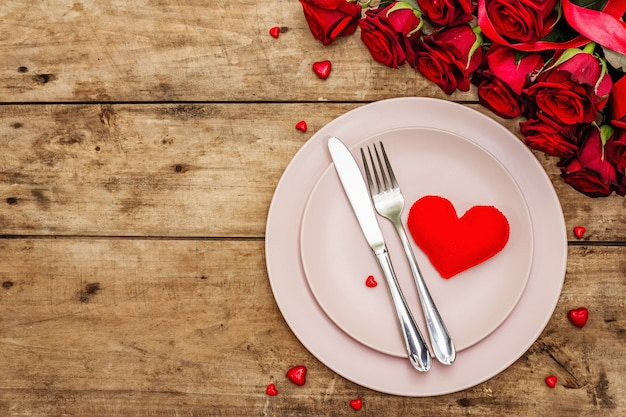 Romantyczny stół obiadowy. koncepcja miłości na walentynki lub dzień matki, sztućce ślubne. bukiet świeżych róż burgundowych, tło vintage desek