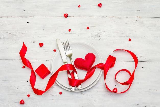 Romantyczny stół obiadowy. koncepcja miłości na walentynki lub dzień matki, sztućce ślubne. miękkie serce z filcu, tło białe deski drewniane