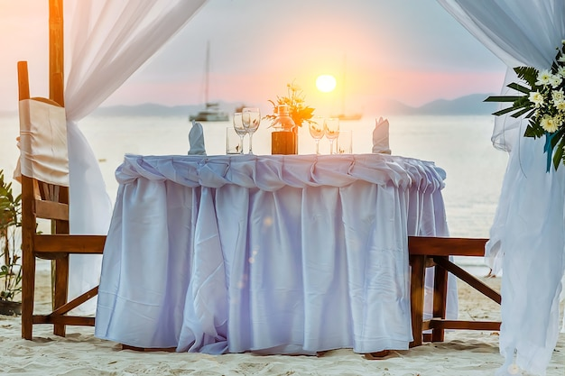 Romantyczny stół obiadowy na tropikalnej plaży podczas zachodu słońca statki na morzu na tle