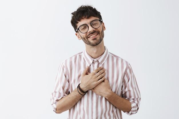 Romantyczny stylowy brodaty facet pozuje na białej ścianie w okularach