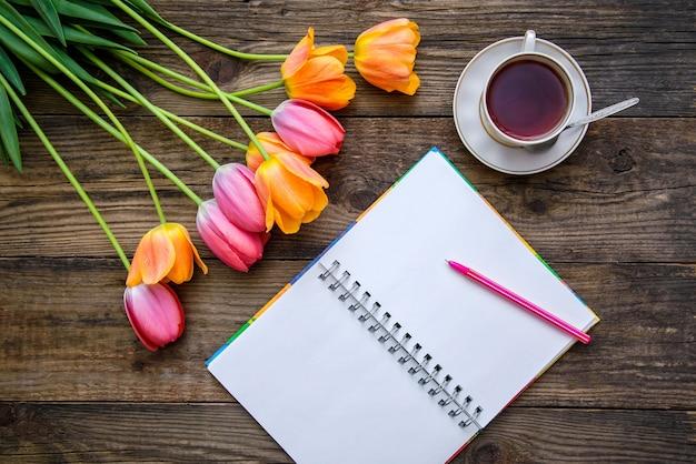 Romantyczny świąteczny obrazek z pięknymi różowymi i pomarańczowymi tulipanami, filiżanką herbaty, notatnikiem na drewnianym rustykalnym tle