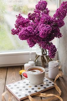 Romantyczny tło z filiżanką herbaty, kwiatów bzu i makaroników.