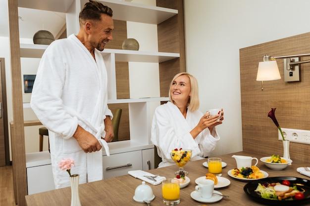 Romantyczny weekend. uśmiechnięta blondynka niosąca filiżankę gorącej kawy i pięknie patrząc na swojego rozpromienionego partnera