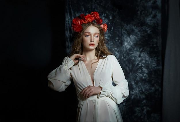 Romantyczny wiosenny portret młodej kobiety blondynka z wieńcem kwiatów czerwonej róży, dziewczyna w lekkiej białej sukni. kobieta z idealną skórą pozuje na ciemnym tle