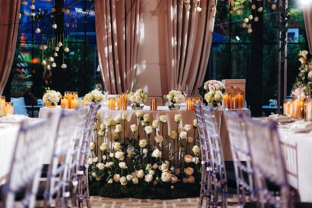 Romantyczny wystrój stołu weselnego z dużymi, bujnymi kwiatowymi bukietami, w tym białe róże, jaskier, perskie jaskry, białe orchidee i świece. zdjęcie wysokiej jakości
