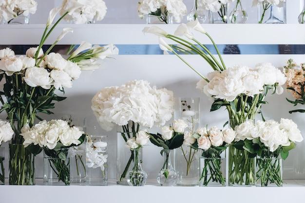 Romantyczny wystrój stołu weselnego z dużymi bujnymi kwiatowymi bukietami, w tym białe róże...