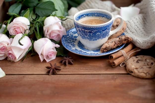 Romatyczna kawa w filiżance na drewnianym tle z szkocką kratą, bukietem białych róż i jesienną przytulnością. dzień dobry. widok z góry. kopiowanie spase