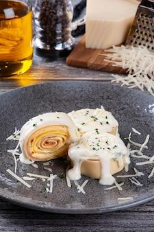 Rondelli z szynką i serem polane białym sosem parmezanowym