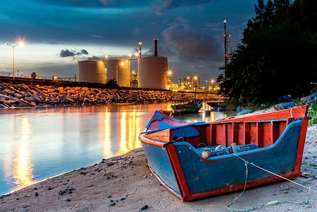 Ropa i gaz rafinerii przemysłowa roślina z naturalną rzeką i łodzią.