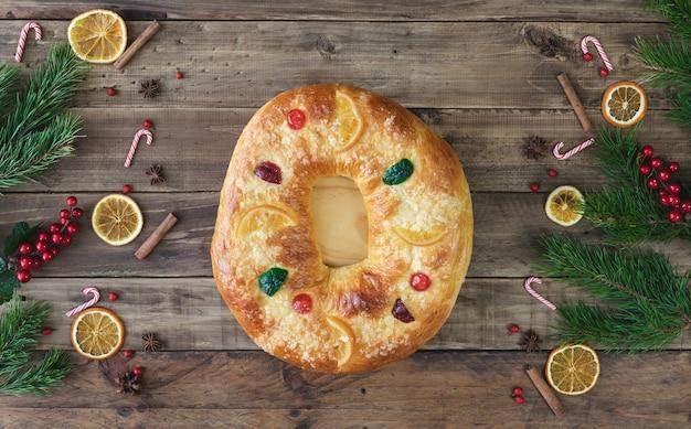 Rosca de reyes na drewnianej podstawie ze świątecznymi dekoracjami