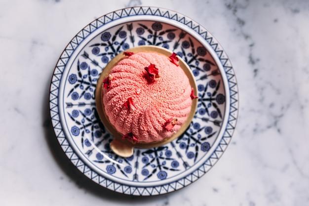 Rose and lychee mousses cake ozdobione płatkami róż w niebieskim i białym talerzu porcelanowym.