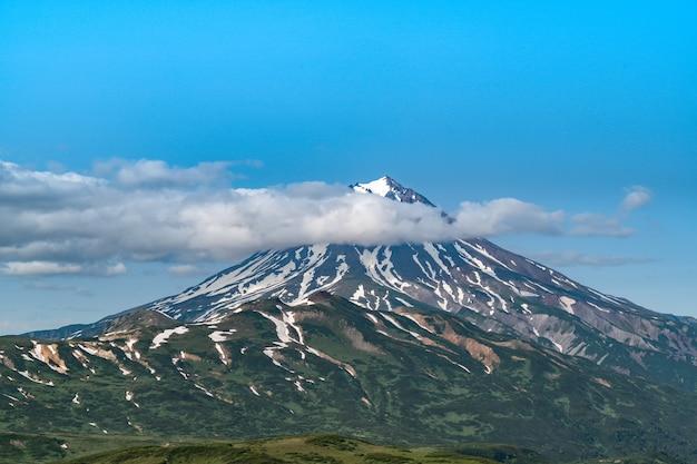 Rosja, kamczatka. piękny widok na wulkan vilyuchinsky w chmurach.