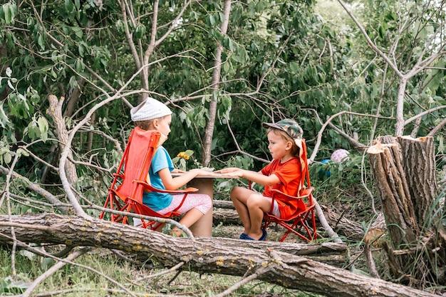 Rosja, lipiec 2020 - małe dzieci, chłopiec i przyjaciółka urządzają piknik i jedzą wśród powalonych drzew latem na wiosce na wsi na wakacjach