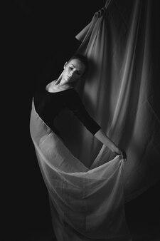 Rosja, moskwa, 1 października 2017: kobieta gimnastyczka pozowanie na czarnym tle i białym suknem. artystyczne zdjęcie gimnastyczki. czarno-białe zdjęcie