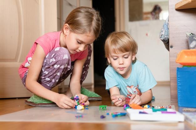 Rosja, moskwa, październik 2020 - dwoje małych szczęśliwych dzieci, czteroletni chłopiec i dziewczynka z siedmioletniego rodzeństwa lub przyjaciół w domu na podłodze razem bawią się i rzeźbią z plasteliny