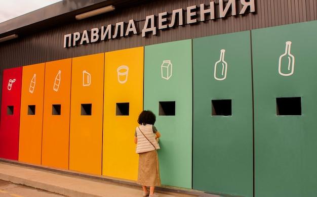 Rosja, sankt petersburg 16 maja 2021: miejsce sortowania odpadów. kobieta wyrzuca śmieci ściśle według kategorii. napis zasady podziału. ekologiczne praktyki w życiu