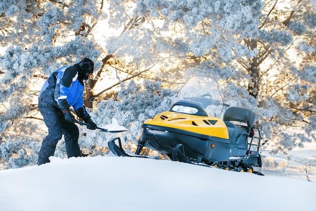 Rosja, sibiria, 24 stycznia 2019: man with stuck snowmobile. wschód słońca, zachód słońca zimowy dzień. zimowa zabawa dla mężczyzny.