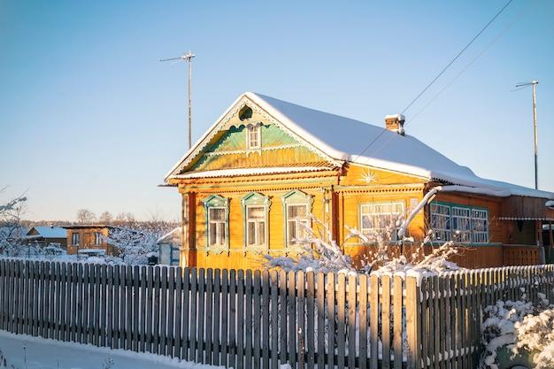 Rosja stary wiejski drewniany dom w rosyjskiej wiosce w zimowym słonecznym dniu. obwód moskiewski, rosja