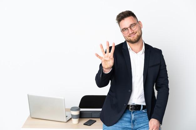 Rosjanin w biurze na białej ścianie szczęśliwy i licząc cztery z palcami