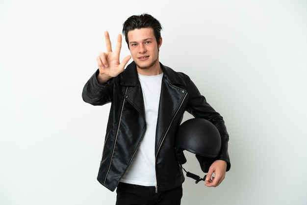 Rosjanin w kasku motocyklowym na białym tle szczęśliwy i liczący trzy palcami