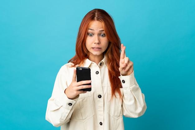 Rosjanka na białym tle na niebiesko przy użyciu telefonu komórkowego z skrzyżowanymi palcami