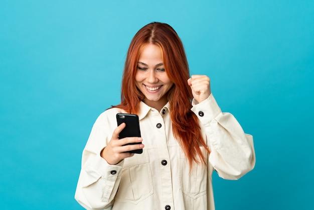 Rosjanka na niebieskim tle za pomocą telefonu komórkowego i robi gest zwycięstwa
