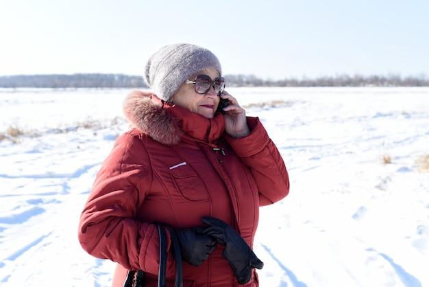 Rosjanka starszy kobieta rozmawia przez telefon przed zaśnieżonym polem