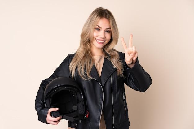 Rosjanka w kasku motocyklowym na białym tle na beżowej ścianie pokazując znak zwycięstwa obiema rękami