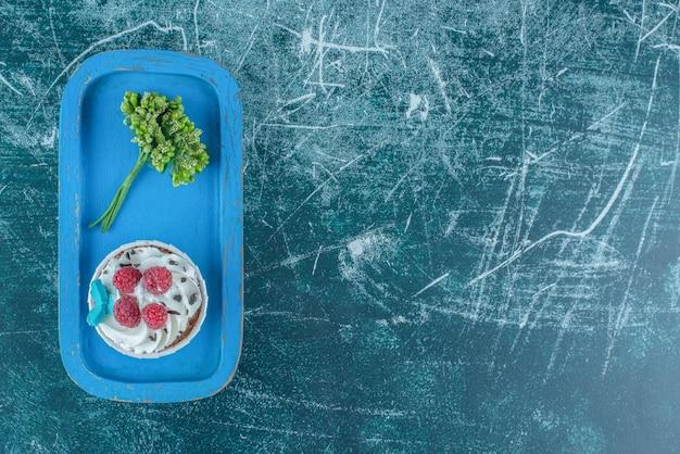 Roślin ozdobnych i ciastko na niebieskim talerzu na niebieskim tle. wysokiej jakości zdjęcie
