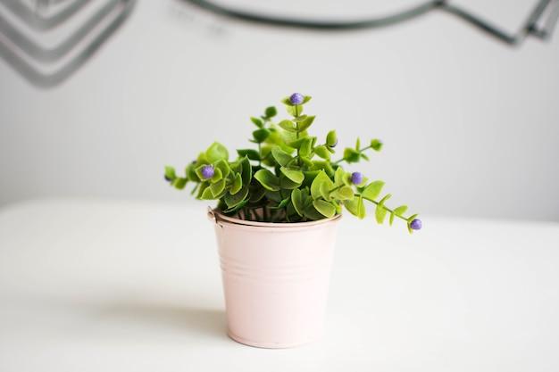 Roślina plastikowa w doniczce na białym stole.