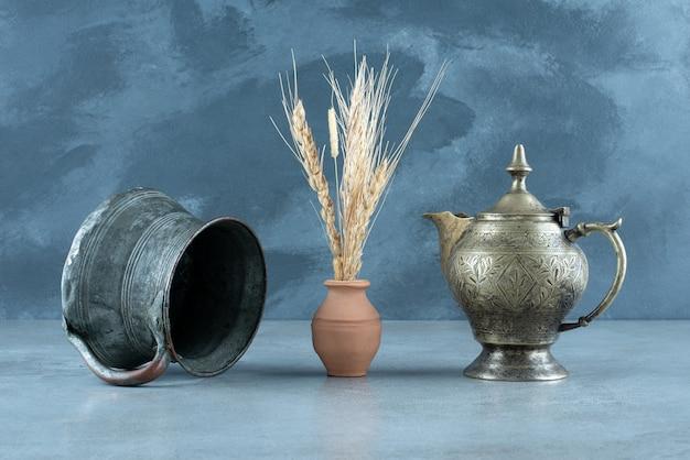 Roślina pszenicy z etnicznym metalowym garnkiem i czajnikiem wokół. zdjęcie wysokiej jakości