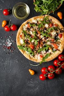 Roślinna włoska pizza z pomidorami na czarnym tle, miejsce na kopię, widok z góry, pionowa