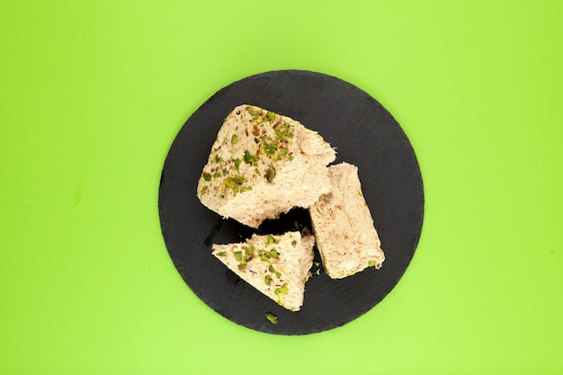 Roślinne pistacje chałwa na czarnym kamieniu orientalne słodycze kopia w zielonym tle