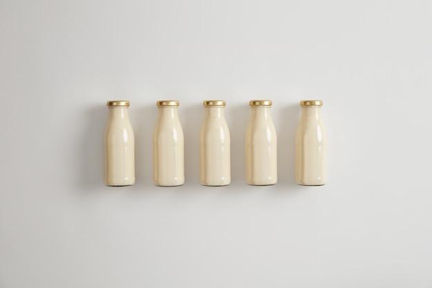 Roślinne wegańskie mleko orzechowe w pięciu szklanych butelkach na białym tle. napój wegetariański jako alternatywa dla produktów mlecznych wytwarzanych ze zbóż, roślin strączkowych, orzechów, nasion. koncepcja reklamy mleka roślinnego